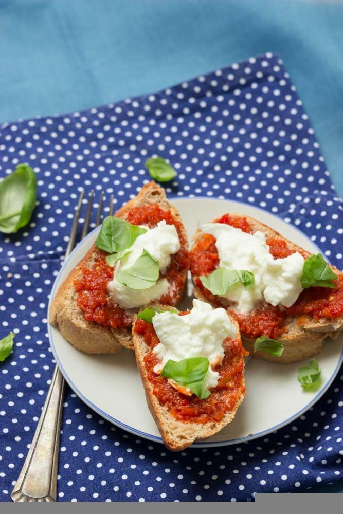 Drei kleine Crostini mit Ajvar und Mozzarella